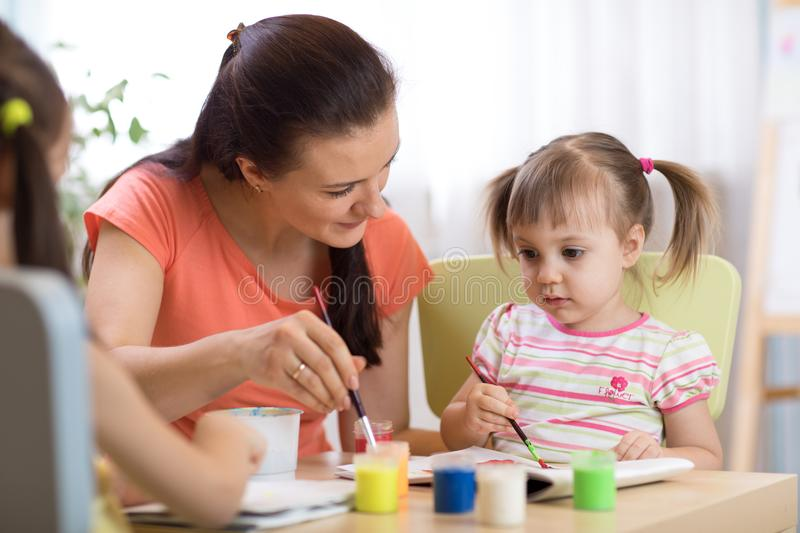 Woman teaches kids painting at kindergarten or playschool royalty free stock photo