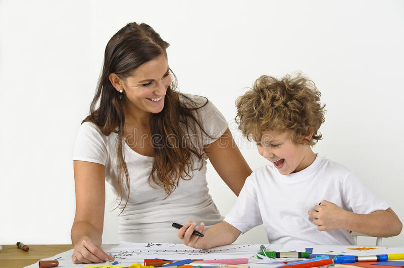 Woman teaches her child how to draw. They are sitting at a table. There are colours on the table stock photos