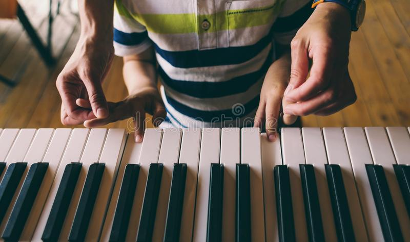 Children`s and women`s hands on the piano keys. A woman teaches her son to play the piano. The boy masters the keyboard musical instrument. A child learns music stock photos