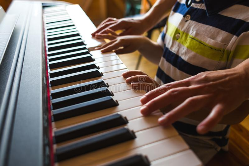 Children`s and women`s hands on the piano keys. A women teaches her son to play the piano. The boy masters the keyboard musical instrument. A child learns music royalty free stock photo