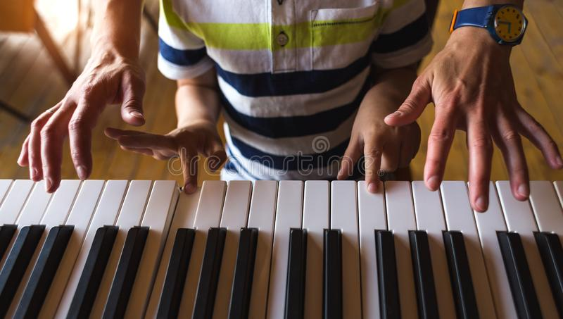 Children`s and women`s hands on the piano keys. A women teaches her son to play the piano. The boy masters the keyboard musical instrument. A child learns music stock photography