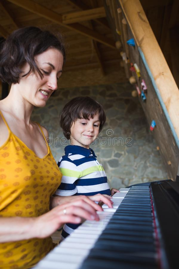 Children`s and women`s hands on the piano keys. A women teaches her son to play the piano. The boy masters the keyboard musical instrument. A child learns music stock photo
