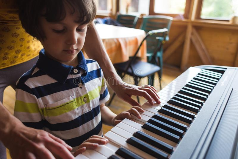 Children`s and women`s hands on the piano keys. A women teaches her son to play the piano. The boy masters the keyboard musical instrument. A child learns music stock images