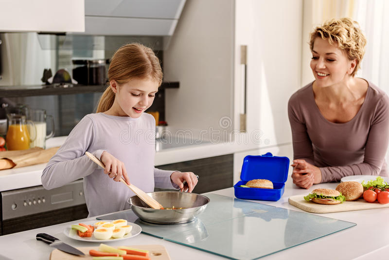 Woman teaching her child to cook stock images