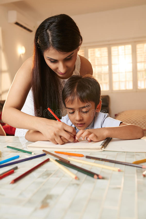 Woman teaching. Hispanic teacher supervising little kid doing homework royalty free stock photos