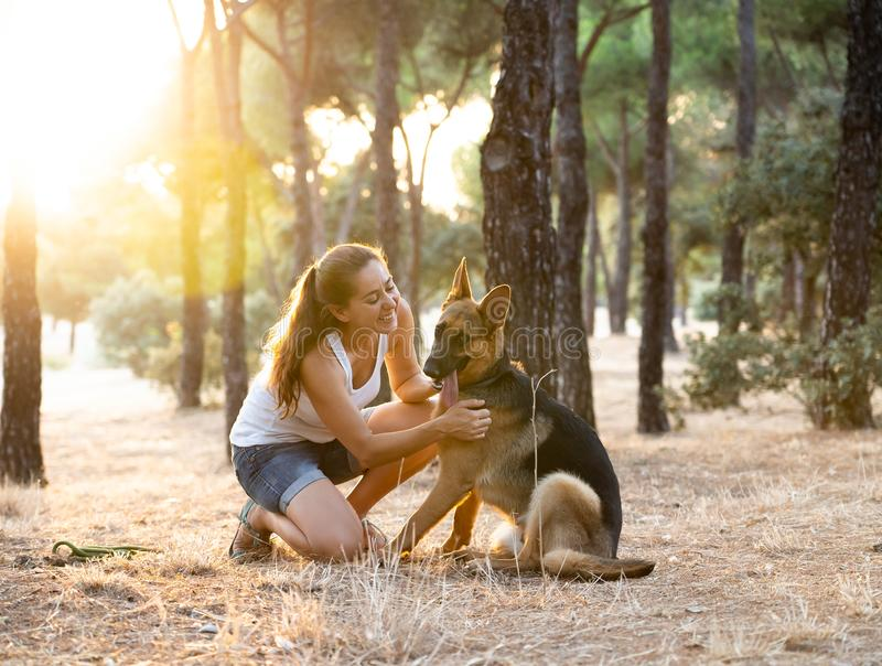 Woman teaching and loving her dog stock image