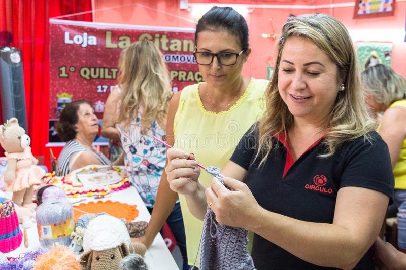 A woman teachs how to Knit crochet. Itajai, Santa Catarina, Brazil - February 22th, 2018: A woman is teaching how to knit in a knitting crochet course at La stock images