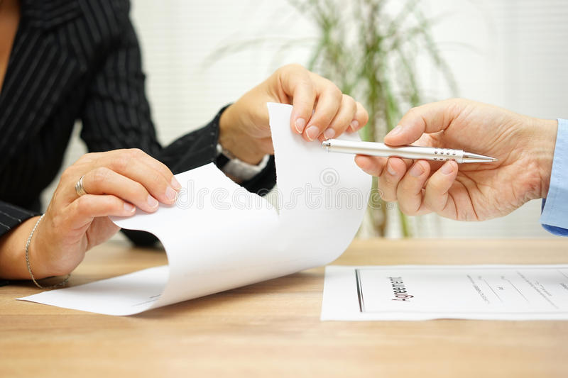 Woman tears agreement documents in front of agent who wants to. Get a signature royalty free stock photo