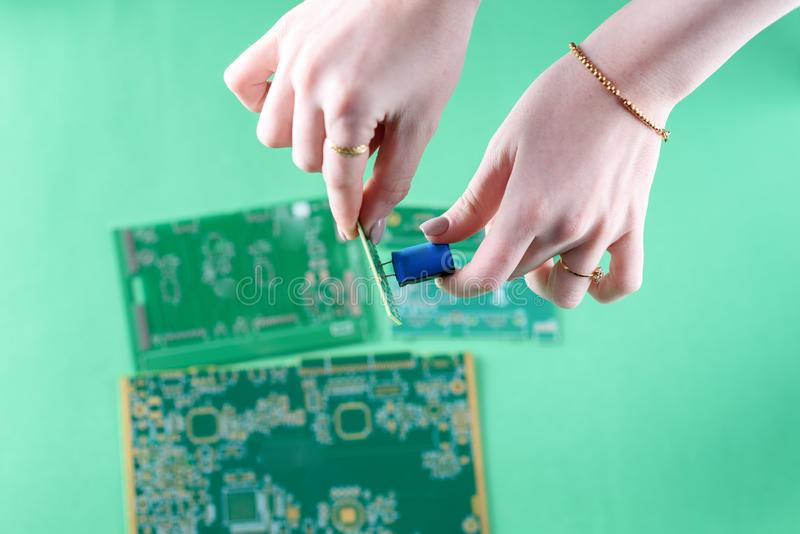 The woman technician is assembling a capacitor on the Circuit Board.Female Technician Inspecting Defective Circuit Board royalty free stock photography