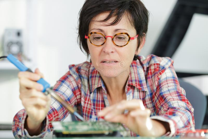 Woman technician repair electronics device toned image. Woman royalty free stock photography