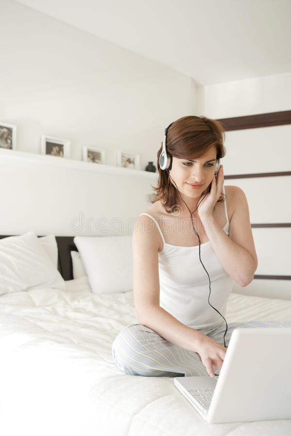 Woman With Technology In Bedroom Royalty Free Stock Photo