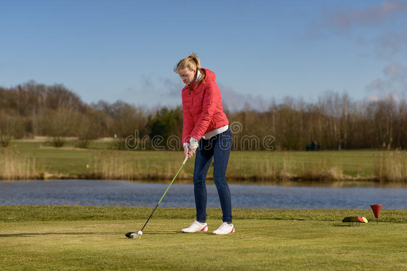 Woman teeing off at a golf course stock images