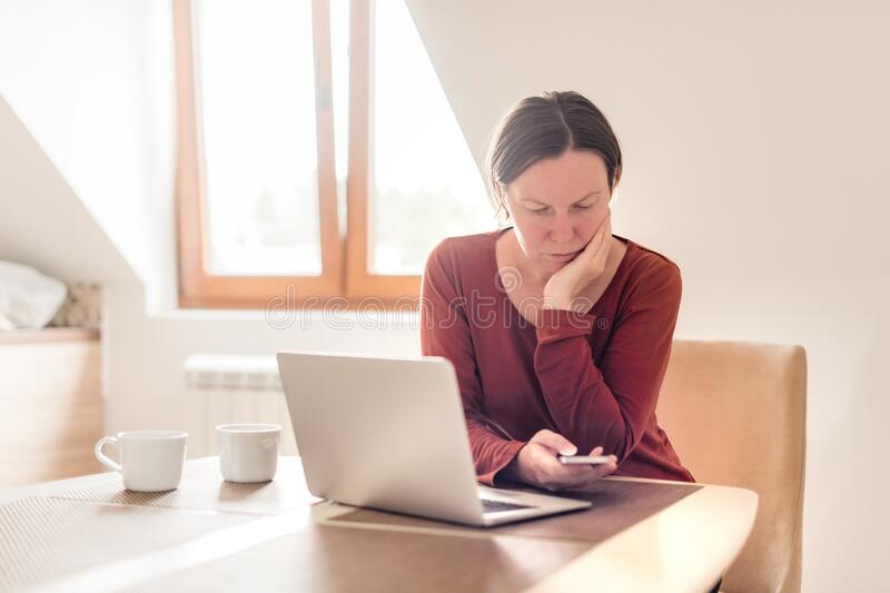 Woman telecommuting in home office interior. Portrait of female freelancer using mobile phone, selective focus royalty free stock image