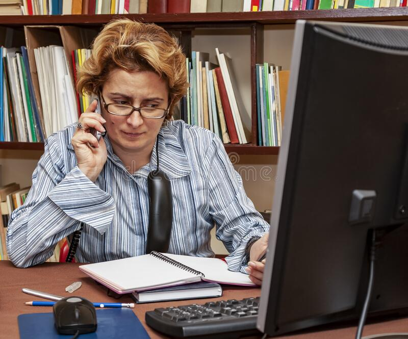 Woman Teleworking. Image of a busy woman teleworking at her desk at the home. Working at home became an important recommendation during the coronavirus outbreak royalty free stock photography