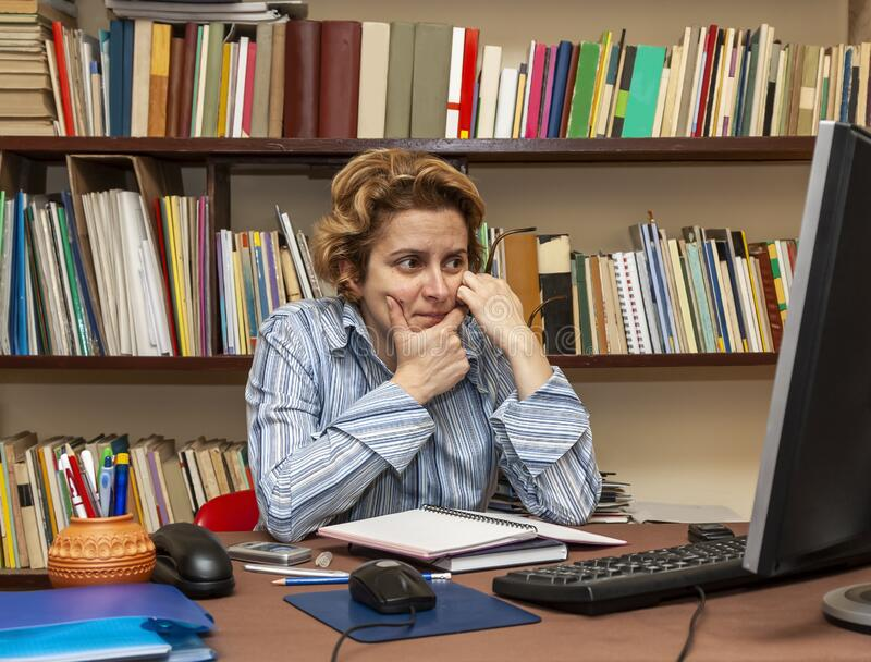 Woman Teleworking. Image of a busy woman teleworking at her desk at the home. Working at home became an important recommendation during the coronavirus outbreak stock images