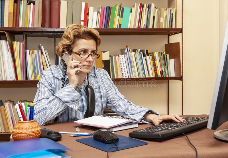 Woman Teleworking. Image of a busy woman teleworking at her desk at the home. Working at home became an important recommendation during the coronavirus outbreak royalty free stock photos