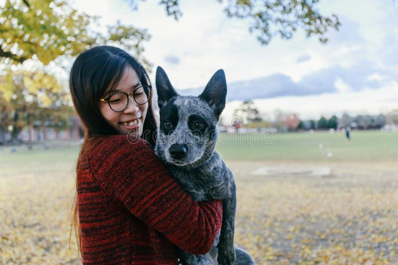 Woman Tenderly Hugging and looking at her Pet Australian doggy. Woman Tenderly Hugging and looking at her Pet Australian cattle dog, black and grey color, in stock images