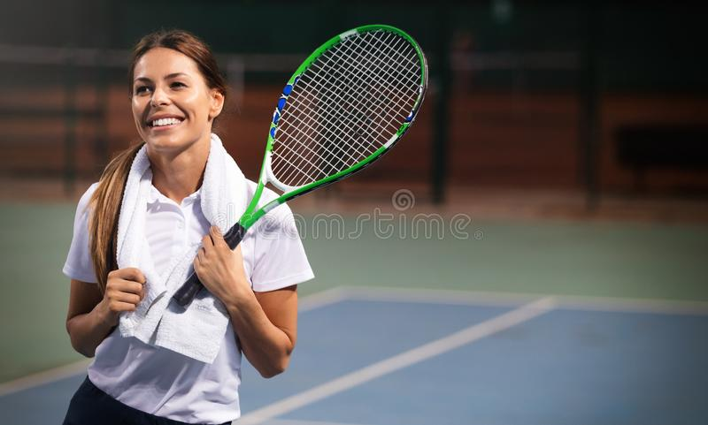 Woman tennis player smiling while holding the racket during tennis match. Female player smiling while holding the racket during tennis match royalty free stock photography