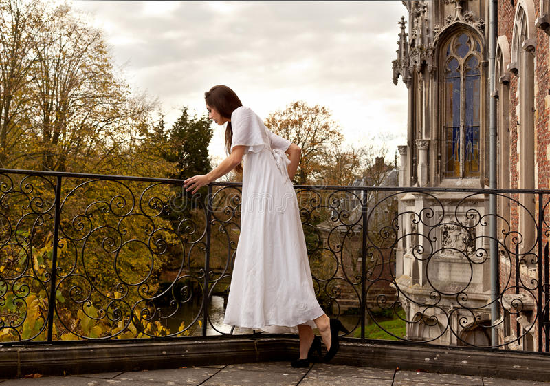 Woman terrace castle park. Woman in a white Victorian dress looking down in the water standing on the terrace of a neo gothic castle in the park stock image