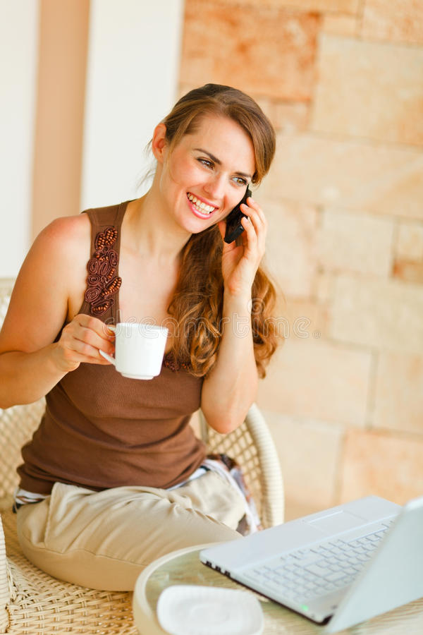 Download Woman On Terrace With Laptop Speaking Mobile Stock Photo - Image: 22516380