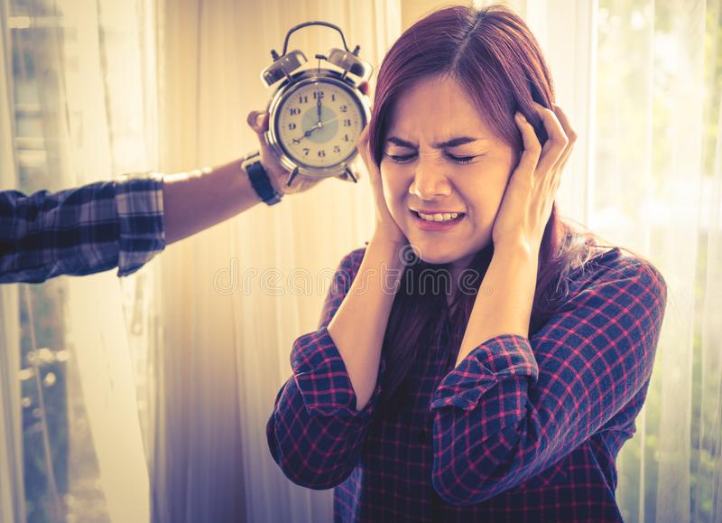 Woman terrified of alarm clock sound. Woman is terrified of alarm clock sound stock photography