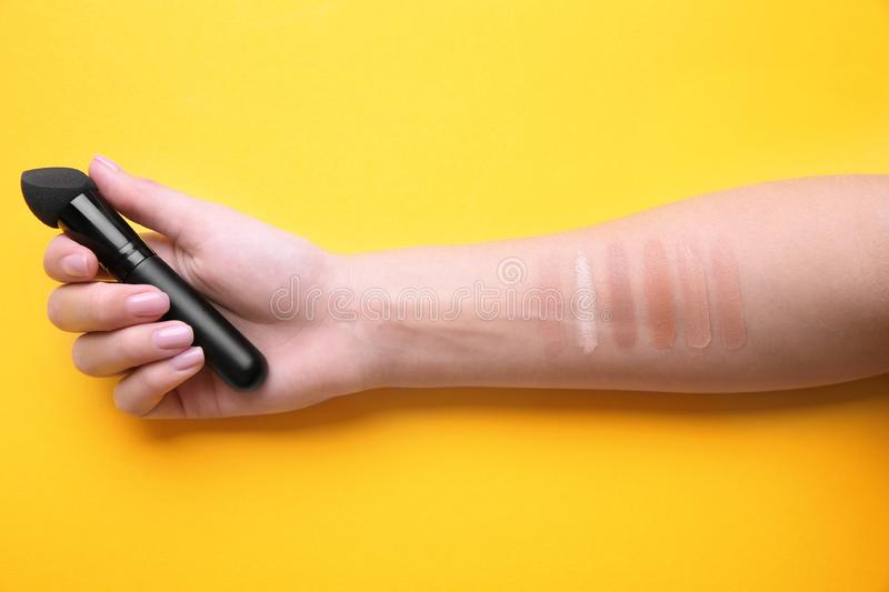 Woman testing different shades of liquid foundation on her hand against color background royalty free stock photography