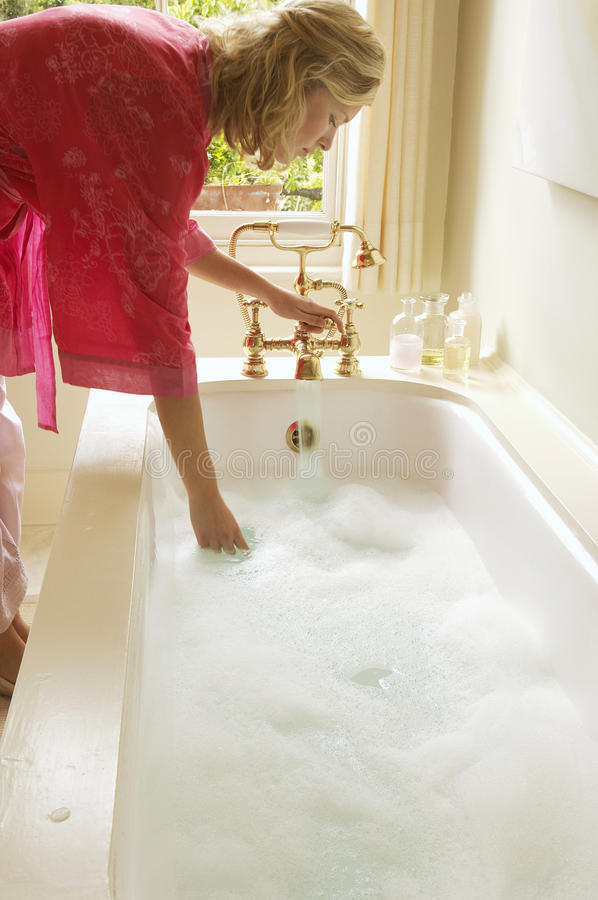 Free Woman Testing Water In Bathtub Filled With Bubbles Royalty Free Stock Photo - 31831175