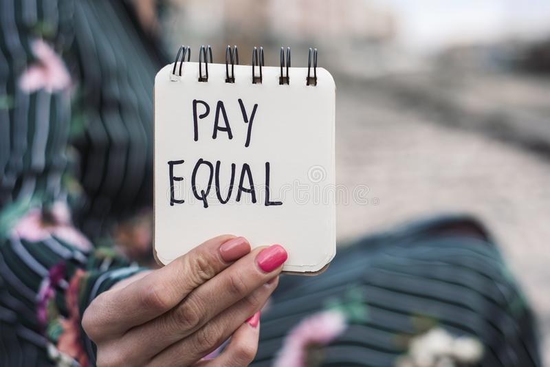 Woman and the text pay equal in a piece of paper. Closeup of a young caucasian woman outdoors showing a notepad with the text pay equal written in it stock photos