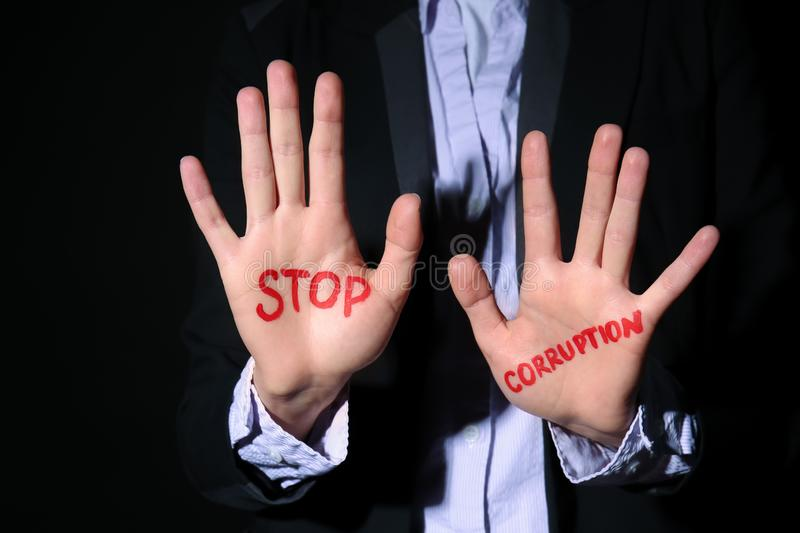 Woman with text STOP CORRUPTION written on her palms against black background, closeup stock photography
