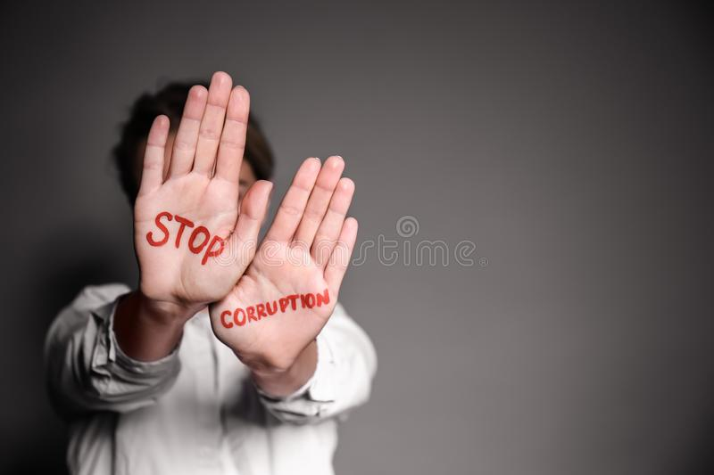 Woman with text STOP CORRUPTION written on her palms against grey background stock photo