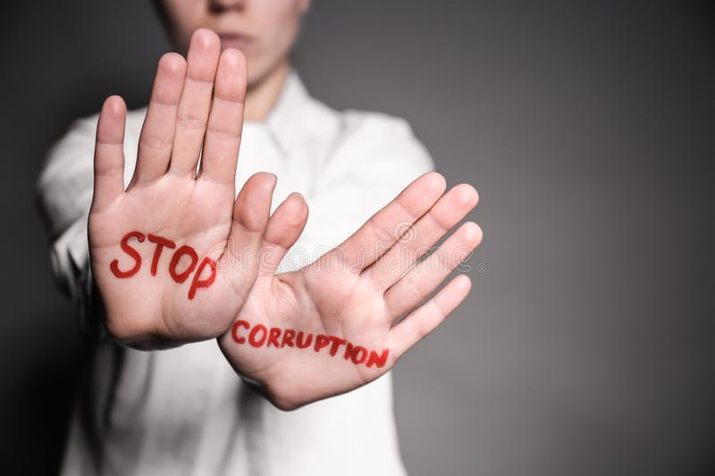 Woman with text STOP CORRUPTION written on her palms against grey background, closeup stock photo