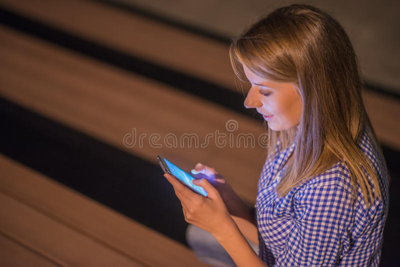 Woman texting. Closeup young happy smiling cheerful beautiful woman looking at mobile cell phone reading sending sms stock photography
