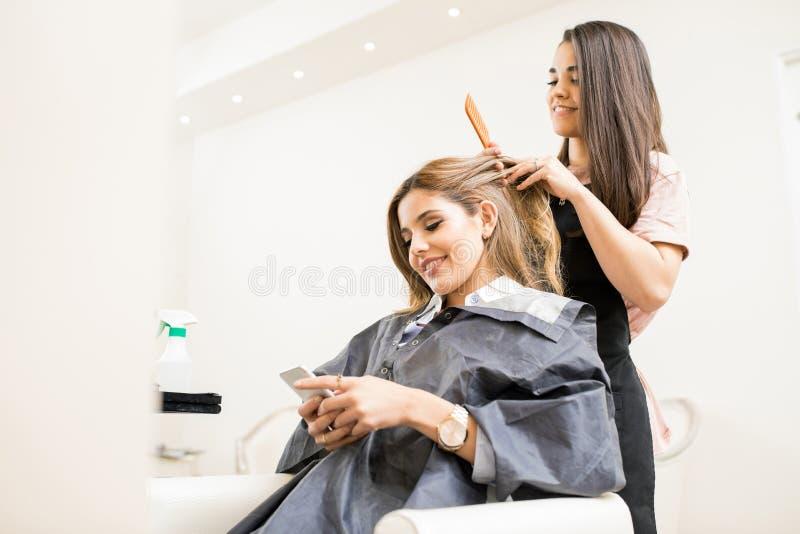 Woman texting at a hair salon royalty free stock image
