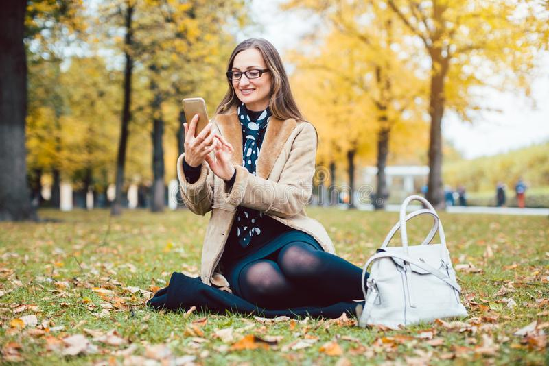 Woman texting with the phone on an autumn lawn in a park royalty free stock photo