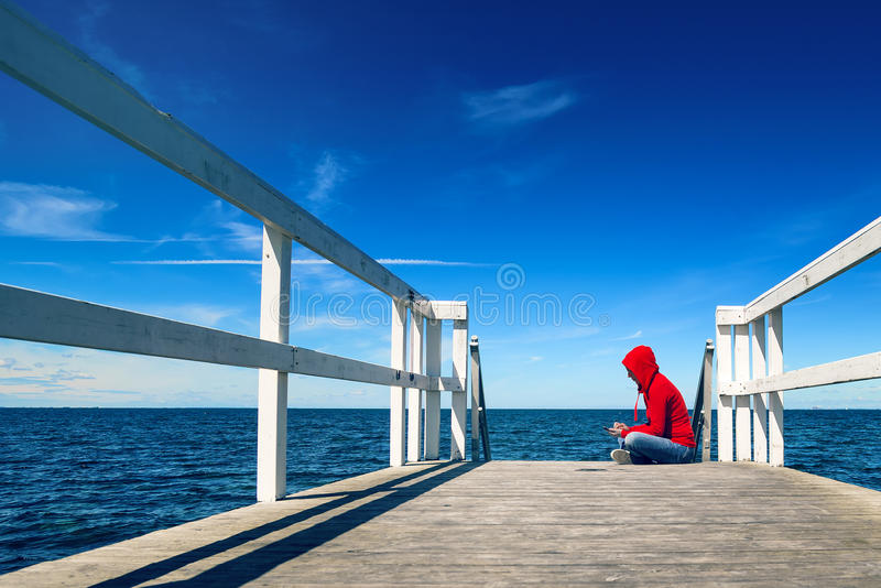 Woman Texting on Smart Phone at Ocean Pier. Alone Young Adult Woman Texting SMS Messages on Smart Phone while Sitting at the Edge of Wooden Ocean Pier stock images