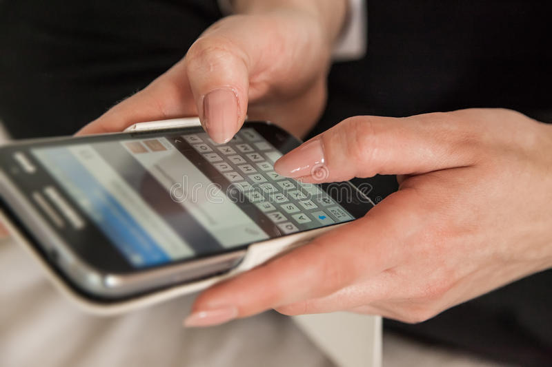 Woman texting sms. Close up of woman hands sending sms on smartphone stock images