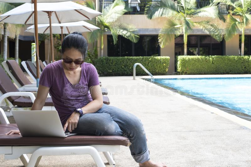 Woman texting and working on laptop by the pool stock photos