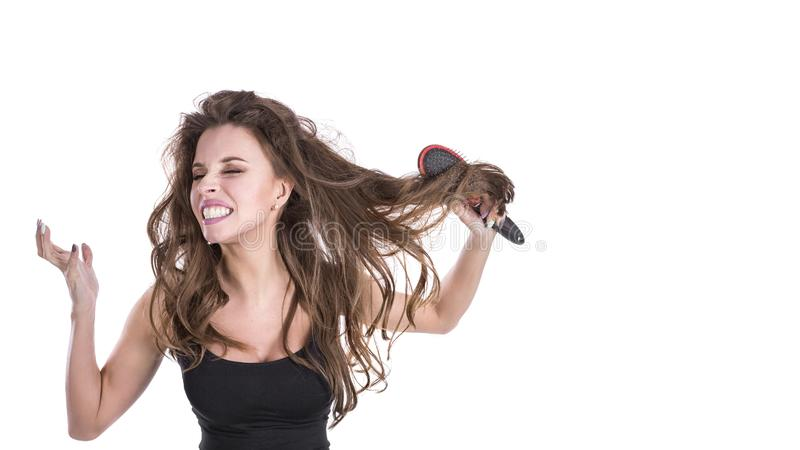 Woman with thick brown tangled hair try to comb hairs but fail. hair healt concept. stock photo