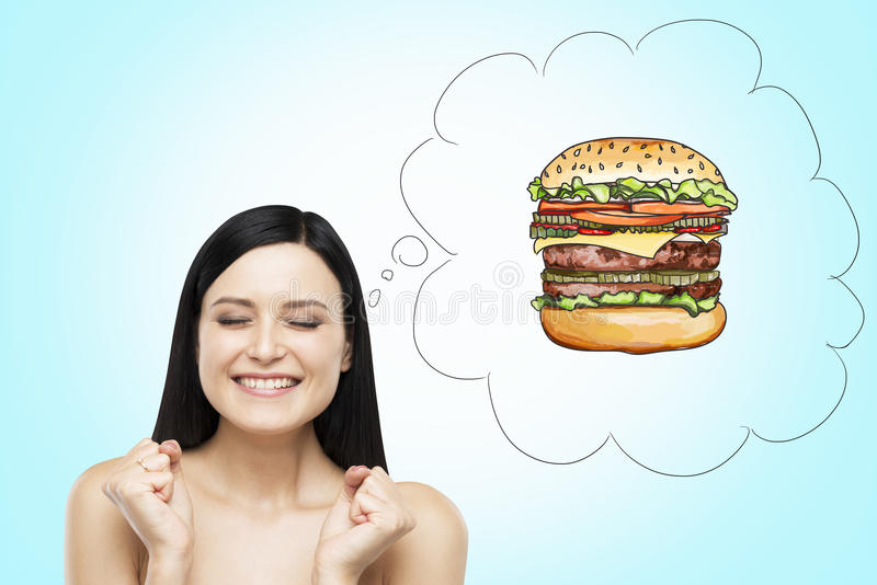 A woman is thinking about burger. A fast food concept. Blue background. A brunette woman is thinking about burger. A fast food concept. Blue background stock image