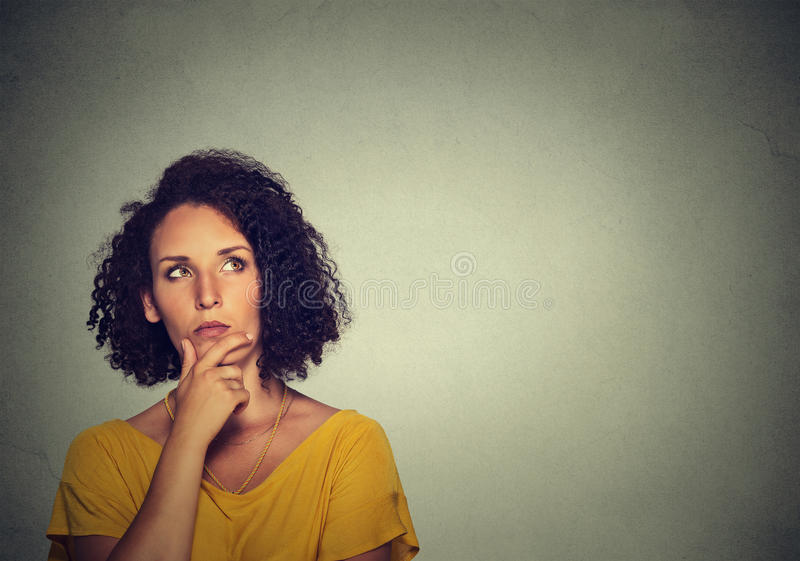 Woman thinking has many ideas looking up. Woman thinking dreaming has many ideas looking up isolated on gray wall background stock photo