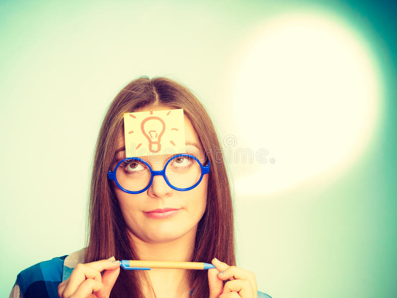 Woman thinking light idea bulb on head. Woman confused thinking seeks solution, paper card with light idea bulb on her head. Girl is trying to create a new idea royalty free stock image