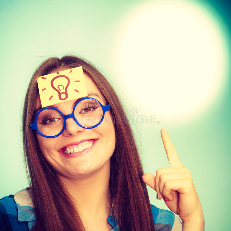 Woman thinking light idea bulb on head, creative girl lots of ideas. Woman confused thinking seeks a solution, paper card with light idea bulb on her head royalty free stock photos