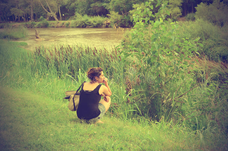 Woman thinking. Picture of beautiful woman thinking alone next to a tranquil and serene river. Image on vintage tone colors stock photo