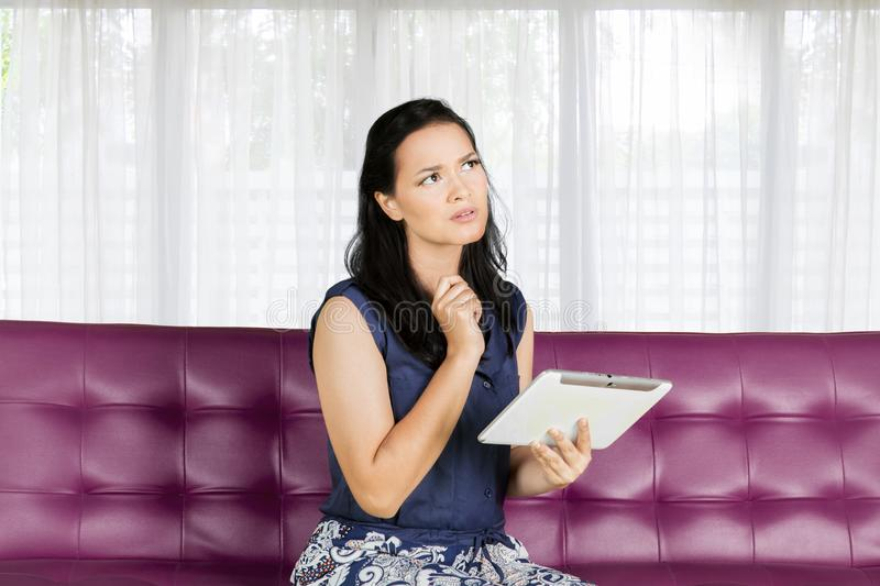 Woman thinking on sofa while holding tablet royalty free stock photography