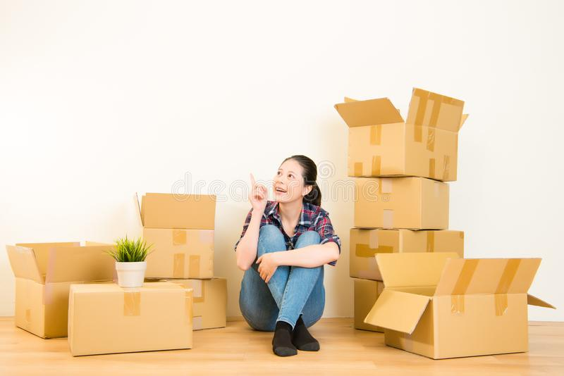 Woman thinking unpacking boxes royalty free stock images