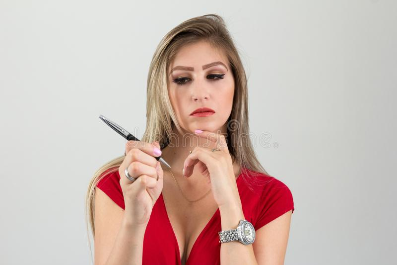 Woman is thinking about what to write. Cleavage. Blonde person a. Woman is thinking about what she will write. Cleavage. Beautiful and person with blonde hair royalty free stock photo