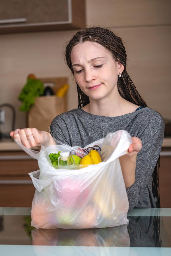 Woman thinks that refuse to use a plastic bag to buy products. Environmental protection and the abandonment of plastic stock photo