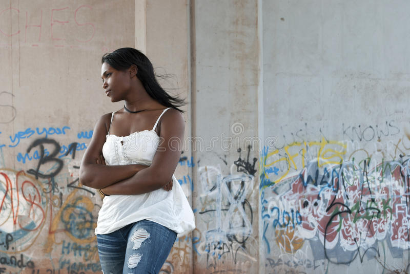 Woman in thought. African-American woman in thought with arms folded in front of a graffiti background stock photo