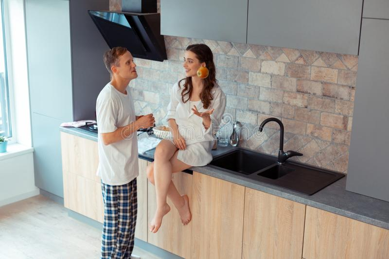 Woman throwing apple while talking to husband in kitchen royalty free stock image