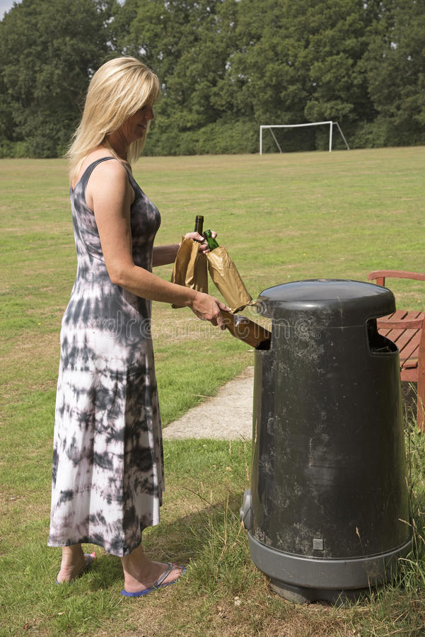 Woman throwing away empty beer bottles. Woman disposing of empty beer bottles in litter bin on a playing field stock image